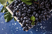Box with ripe sweet grapes on color table