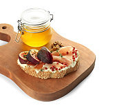 Tasty sandwich with ripe fig and honey on white background