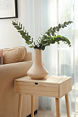 Vase with green eucalyptus branches on table in room