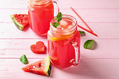 Mason jars of fresh watermelon lemonade on color wooden table