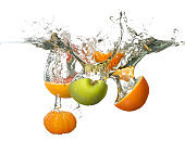 Falling of fruits into water on white background