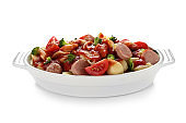 Delicious pasta with sausage and sauce in ceramic dish on white background