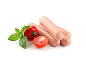 Tasty sausages with tomatoes and basil on white background