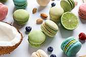 Tasty macaroons, coconut, berries and cut lime on white table