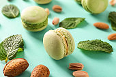 Tasty macaroons with mint and nuts on color background, closeup