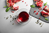 Flat lay composition with glass cup of red tea and pomegranate on grey background