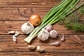 Fresh dill with garlic and onion on wooden background