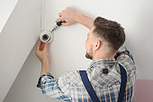 Electrician installing surveillance camera