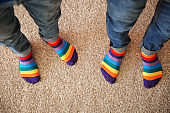Gay couple with colorful socks standing on carpet, top view