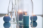 Glassware with beautiful burning candles on table with reflection
