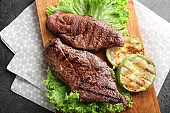 Tasty grilled meat with squash and lettuce on wooden board
