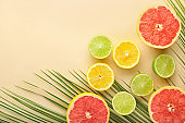 Summer composition with tropical fruits on light background