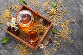 Hot tea with dried chamomile flowers in wooden box