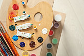 Tubes with color paints of professional artist and palette on table, top view