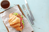 Wooden board with tasty croissant sandwich and cup of tea on light table