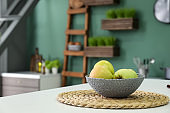Wicker bowl with fresh apples on light table in kitchen