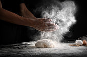 Man clapping hands and sprinkling flour over dough on black background