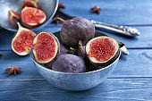 Bowl with fresh ripe figs on color wooden table