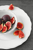 Bowl with fresh ripe figs on grey table