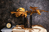 Retro alarm clock with golden tropical leaves on table near dark wall