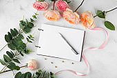 Composition with beautiful flowers and notebook on light background