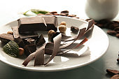 Plate with delicious chocolate, nuts and shavings on table