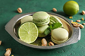 Plate with tasty macaroons, pistachio nuts, mint and lime on color table
