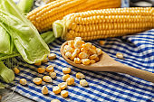 Spoon with corn kernels on table