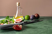 Plate with delicious fig salad on color table