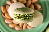 Plate with sweet macaroons and pistachio nuts, closeup