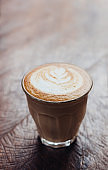Close up coffee cup with latte art on grunge wood table at cafe