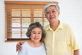 Asian senior couple embrace togerther and looking at camera in living room at home.Happy retirement lfie.aging at home concept.