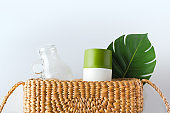 zero waste concept.top view wicker bag with glass bottle and reusable cup with green leaf on white table.eco friendly for environment.plastic free