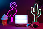 Summer items with flamingo, cactus, sunglasses and blank light box with neon pink and blue light on table with monstera leaf.Mock up space for adding text.