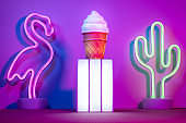 Summer with lightbox and flamingo,cactus and ice cream with neon pink and blue and green light on table with copy space.Trendy vacation holiday background.
