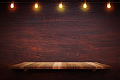 Empty brown plank wood shelf at black red wooden wall background with light bulbs string,Mockup for display or montage of product or design.