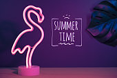 Summer time with pink flamingo and monstera leaf with neon pink and blue light.vacation background.