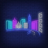 City buildings and road neon sign