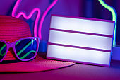 Summer time with blank light box on hat with sunglasses refection flamingo and cactus neon pink and blue and green light on table with copy space.Trendy vacation holiday background.