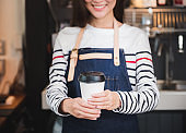 asian woman barista wear jean apron holding hot coffee cup served to customer with smiling face at bar counter,Cafe restaurant service concept.waitress working.