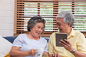 Asian senior couple using table compute and drink coffee sitting at sofa in living room at home.senior with technology lfiestyle.aging at home concept.