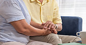 Close up Asian senior couple encouraging together by holding hand each other at sofa in living room at home.Happy retirement lifestyle.aging at home