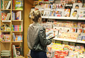 Woman buying a magazin in a store