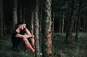 Young depressed man sitting alone in the forest