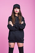 Strong and confident young woman in black clothes against pink background