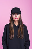 Cofident young woman in black clothes against pink background