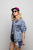 Stylish woman wearing sunglasses and denim jacket