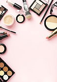 Makeup products, decorative cosmetics on pink background  flat lay toned.  Fashion and beauty concept. Top view. Copy space.