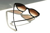 Black stylish sunglasses on a white background  with sunlight shadows .copy space. creative concept