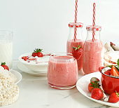 Strawberry smoothie or milkshake in a glass on marble background. Healthy food for breakfast and snack. copy space